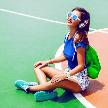 Lifestyle bright fashion portrait of young fit stylish woman posing at sport ground, wearing trendy neon swag look, sunglasses and backpack, listening her favorite music on big earphones stock vector