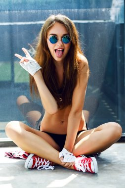 Indoor bright fashion summer portrait of stylish cheeky hipster woman, showing her tongue, have long brunette hairs perfect tanned fit slim body, wearing sneakers bikini pants and young sunglasses stock vector