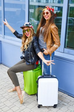 Young pretty friends posing with their luggage waiting for taxi, holding map , ready for new trip. Two girls traveling together, wearing bright clothes leather jackets and swag hats, urban style. stock vector