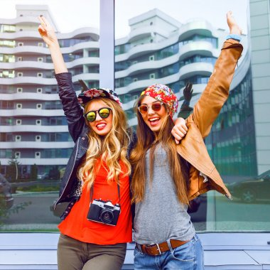Two pretty girls best friends screaming laughing and put their hands to the air, enjoy their freedom and friendship, wearing stylish hipster swag fright outfits hats and sunglasses, urban style stock vector