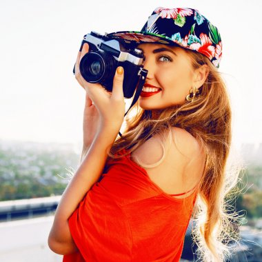 Young sexy smiling photographer woman, holding and making picture on retro vintage camera, wearing swag floral bright cap, amazing view on the city from roof, joy and happiness stock vector