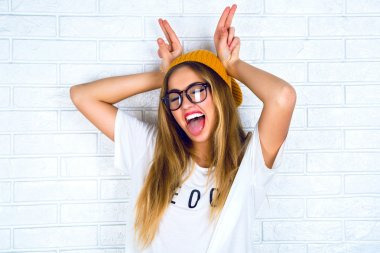 Young girl doing emotion, hands raised up in the form of rabbit ears . Dressed in a white shirt, yellow hat, glasses and bright lips, trendy clothes stock vector