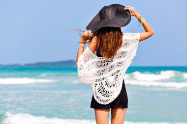 woman posing back near blue sea