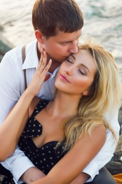 handsome man kissing his brunette girlfriend