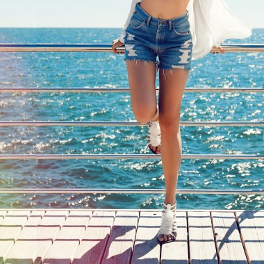 Woman with sexy legs posing near sea