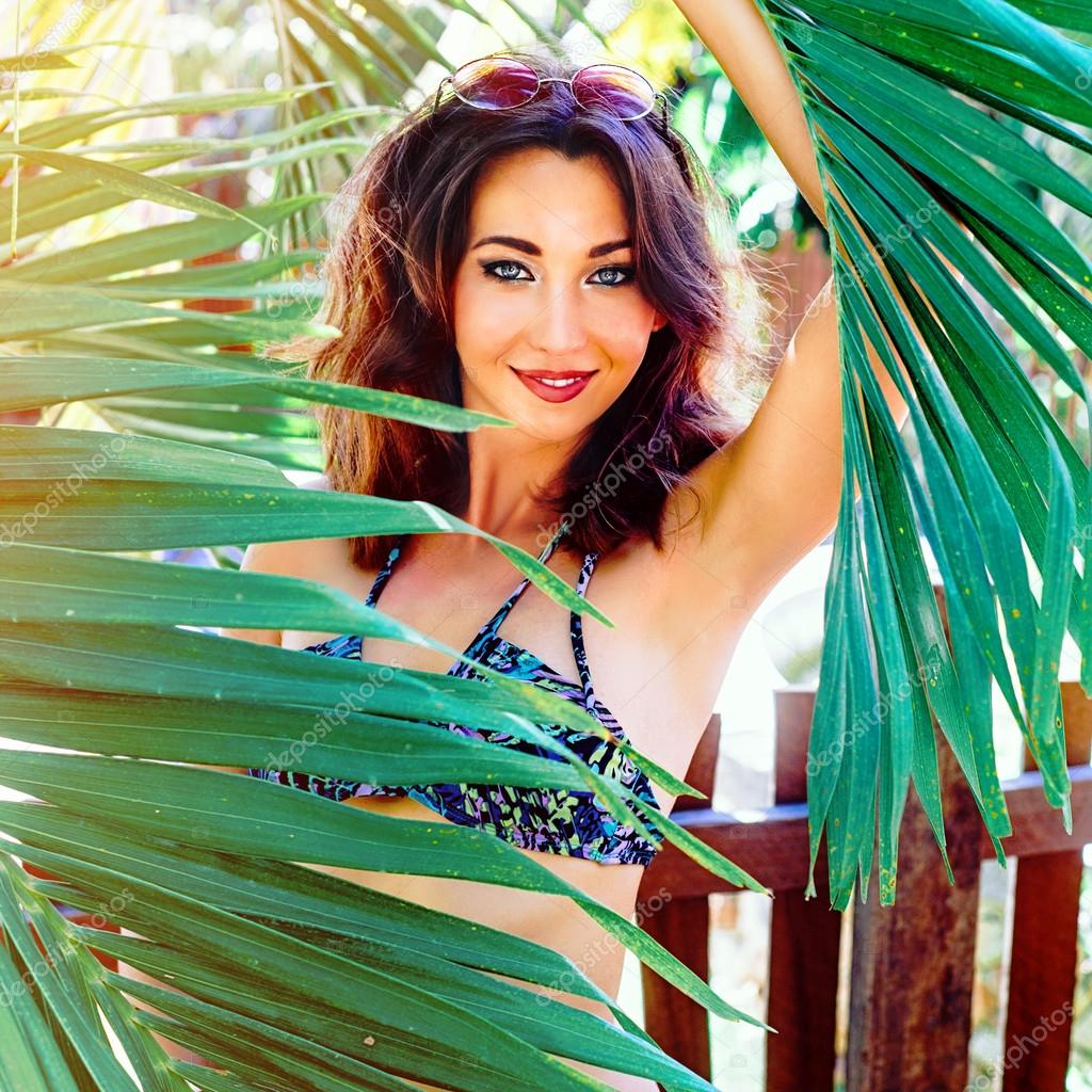 342c714d3141f Tropical fashion portrait of beautiful smiling brunette woman with curled  hairstyle and bright make up, wearing bikini and posing at palms garden, ...