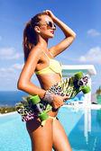 žena s dokonalým tělem držení skateboardu