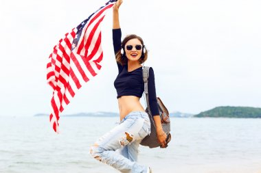 woman posing at the beach with american flag