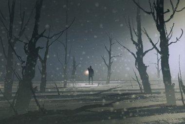 man holding lantern stands in dark forest with fog