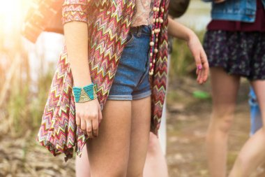young girl in denim shorts, jewelry accessories.
