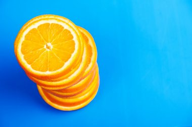 stack of sliced oranges on a blue background