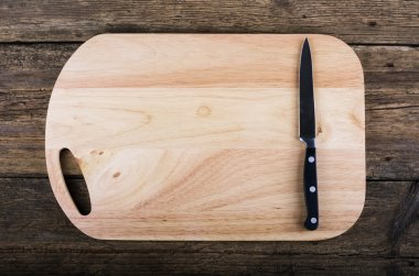 Empty chopping board with a sharp paring knife on a distressed grunge wooden table in a rustic kitchen, overhead view with a vignette and copyspace