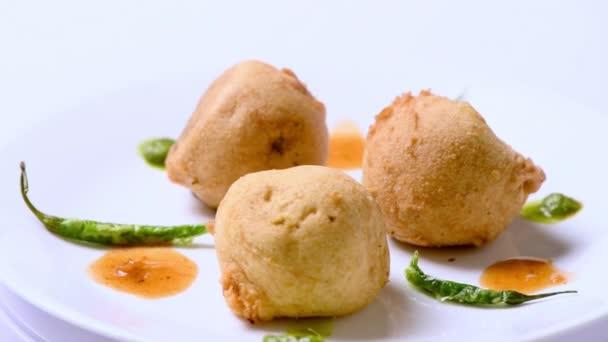 Lahodné bramborové vadas (podobné vadapav), nebo smažené brambory v kulovitém formátu, s zdobení, rotující na bílém stole. Tohle je indické jídlo.