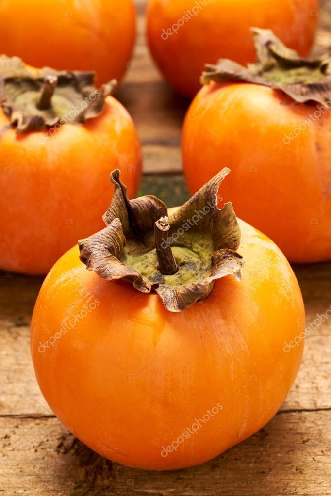 Yummy persimmon on a wooden board