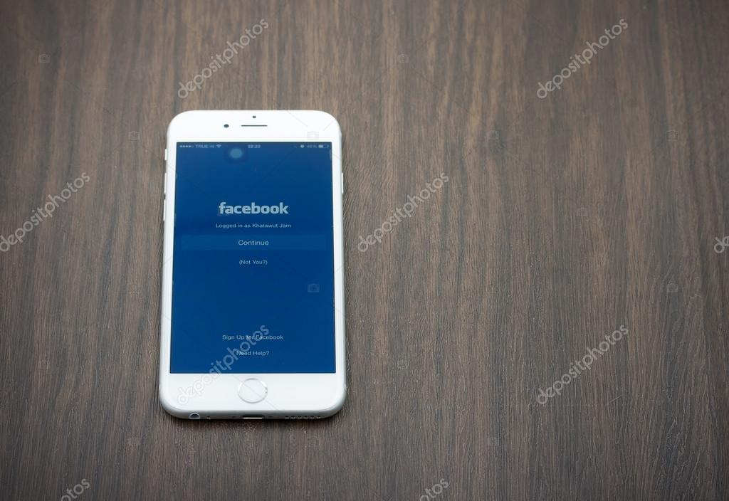 Apple Iphone 6 in white color with facebook page laying on woode