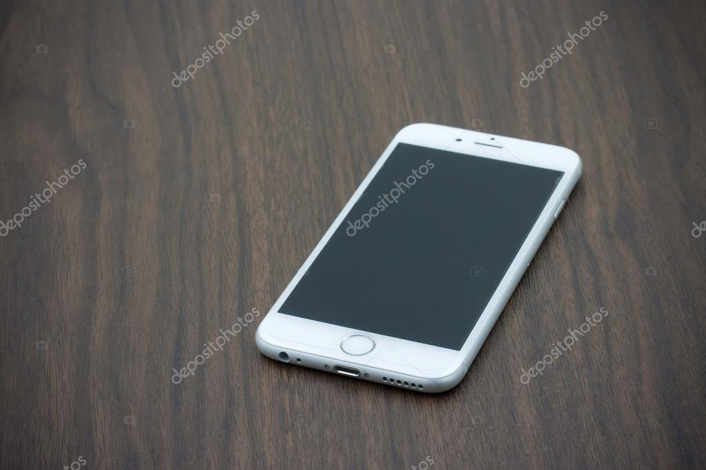Apple Iphone 6 in white color with blank screen laying on wooden