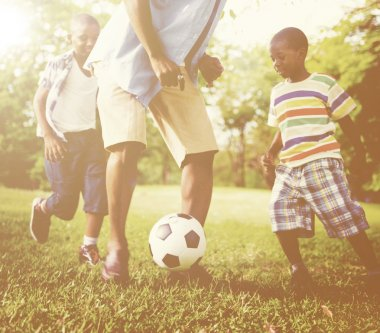 father playing football with children