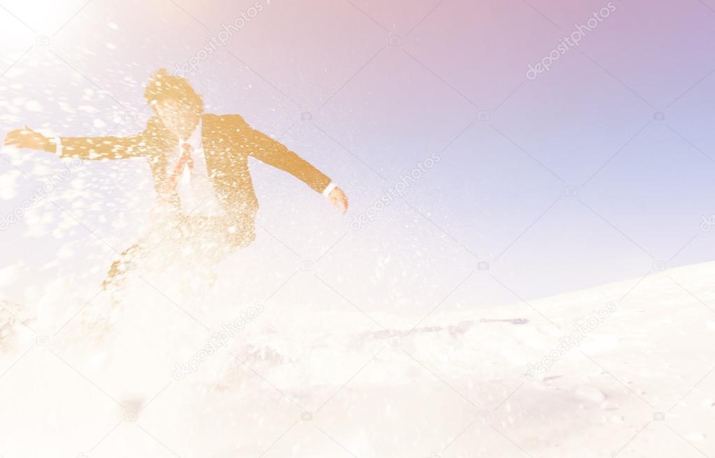 Businessman snowboarding on mountain