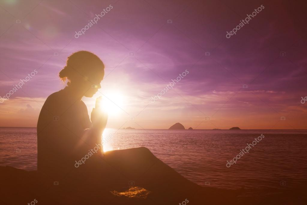 Young woman praying at sunsets