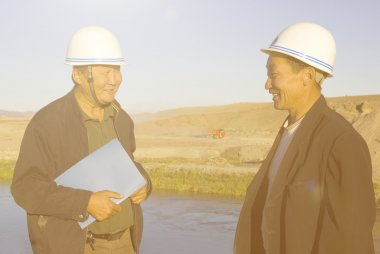 construction workers in helmets discussing and planning