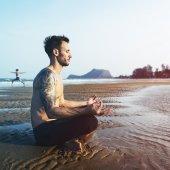 Man doin Yoga on Beach