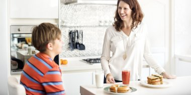 Happy mom with son at home kitchen