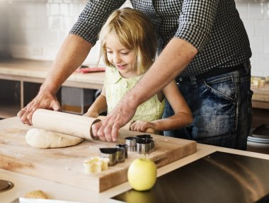 Little girl with father making cookies