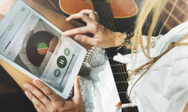 girl with guitar using tablet