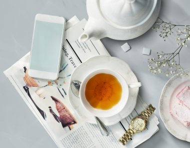 Tea, Newspaper, Watch on desk.