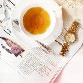 Fotografie ruky hodinky a tea cup na stole