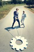 Unternehmer und Unternehmerin ziehen Zahnrad auf Straße