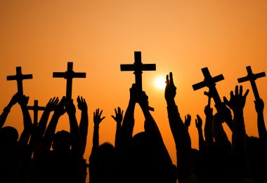 People holding crosses at sunset