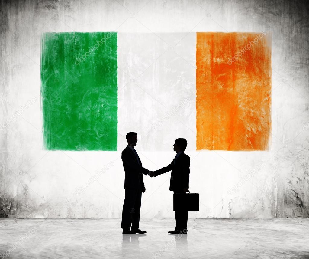businessmen shaking hands with flag of ireland u2014 stock photo