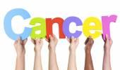 Fotografie rozmanité ruce držící slovo rakovina