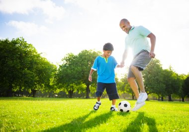 Boy playing soccer with father