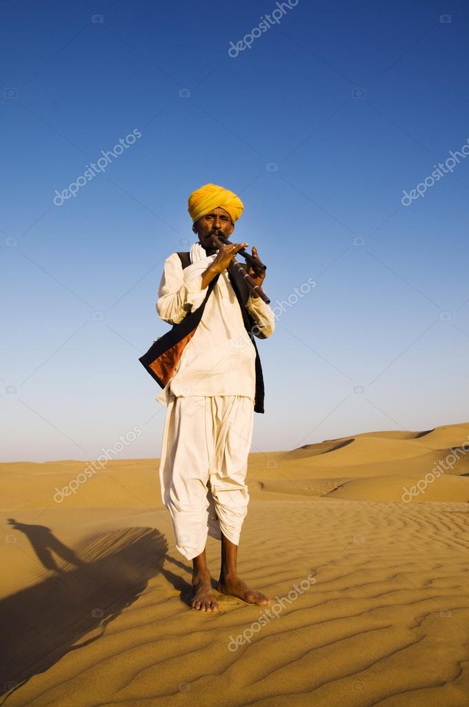 Indian man playing wind pipe in desert