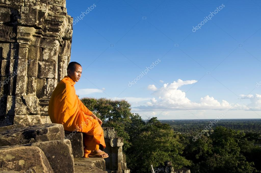 Monk sitting on rocks of old building