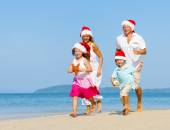 Family on beach in Christmas hats