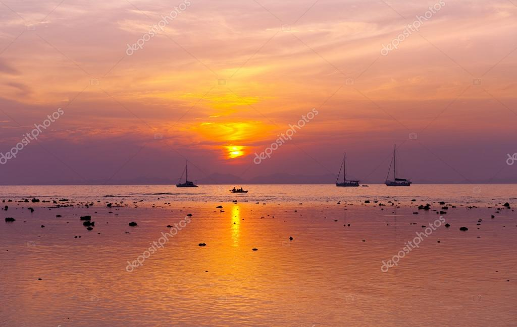 Dreamy beach sunset with yachts