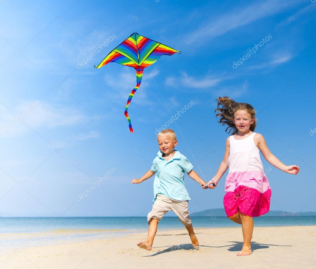 Sister and brother playing with kite on beach