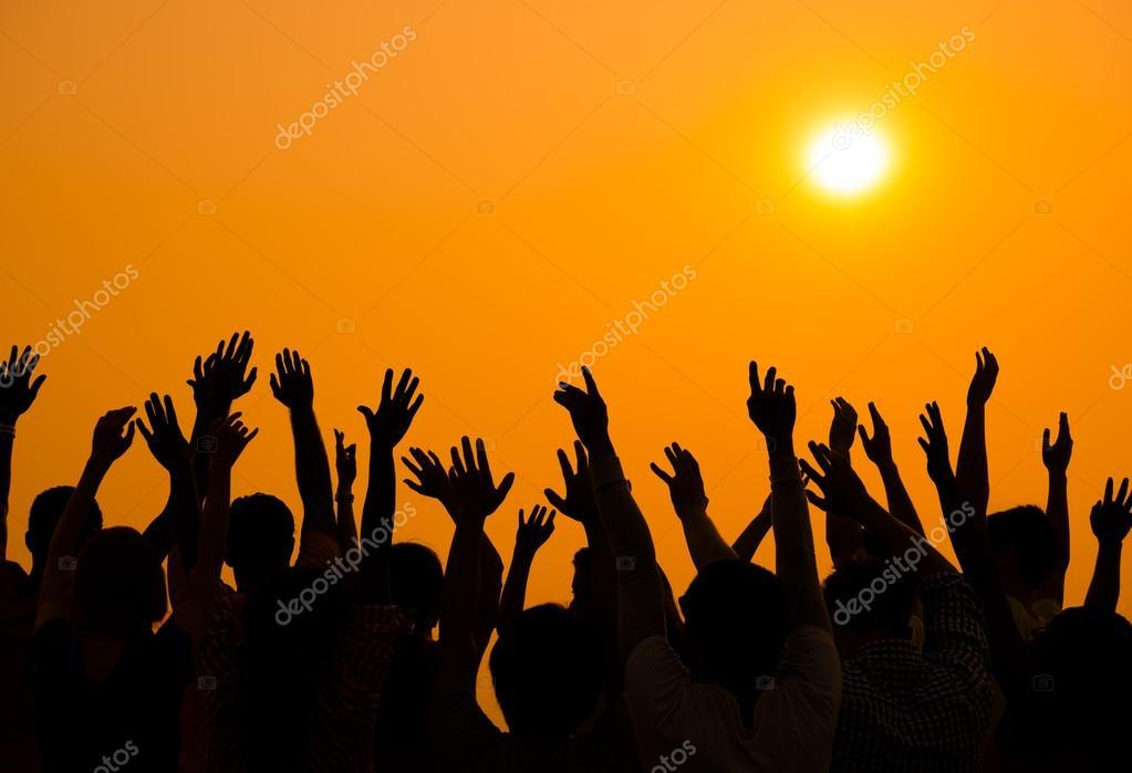 People raised hands up on sunset