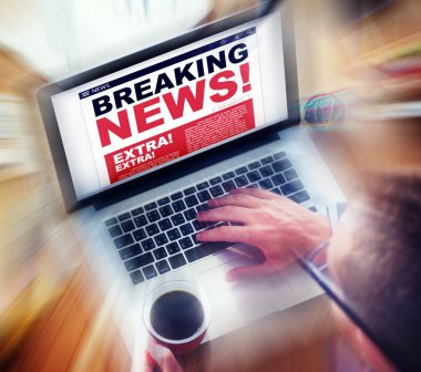 Man using laptop with Breaking News