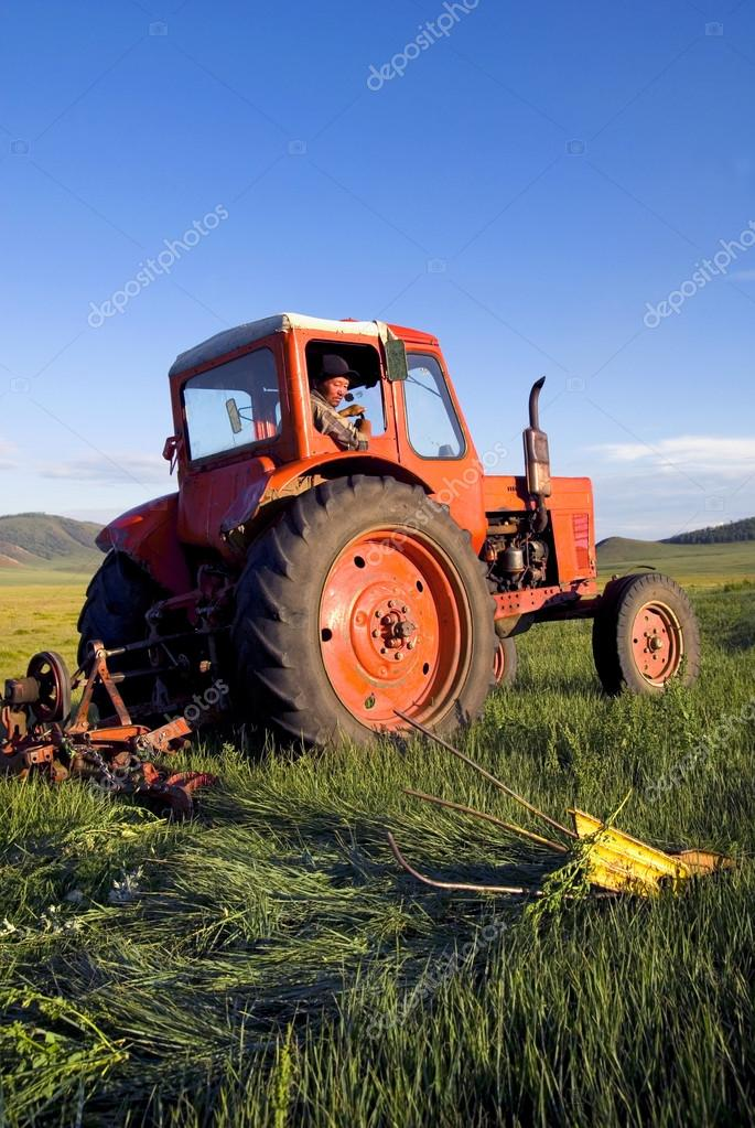 Farmer Driving His Tractor On The Field