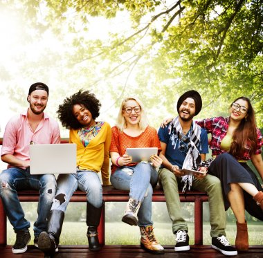 happy friends sitting on bench with laptop