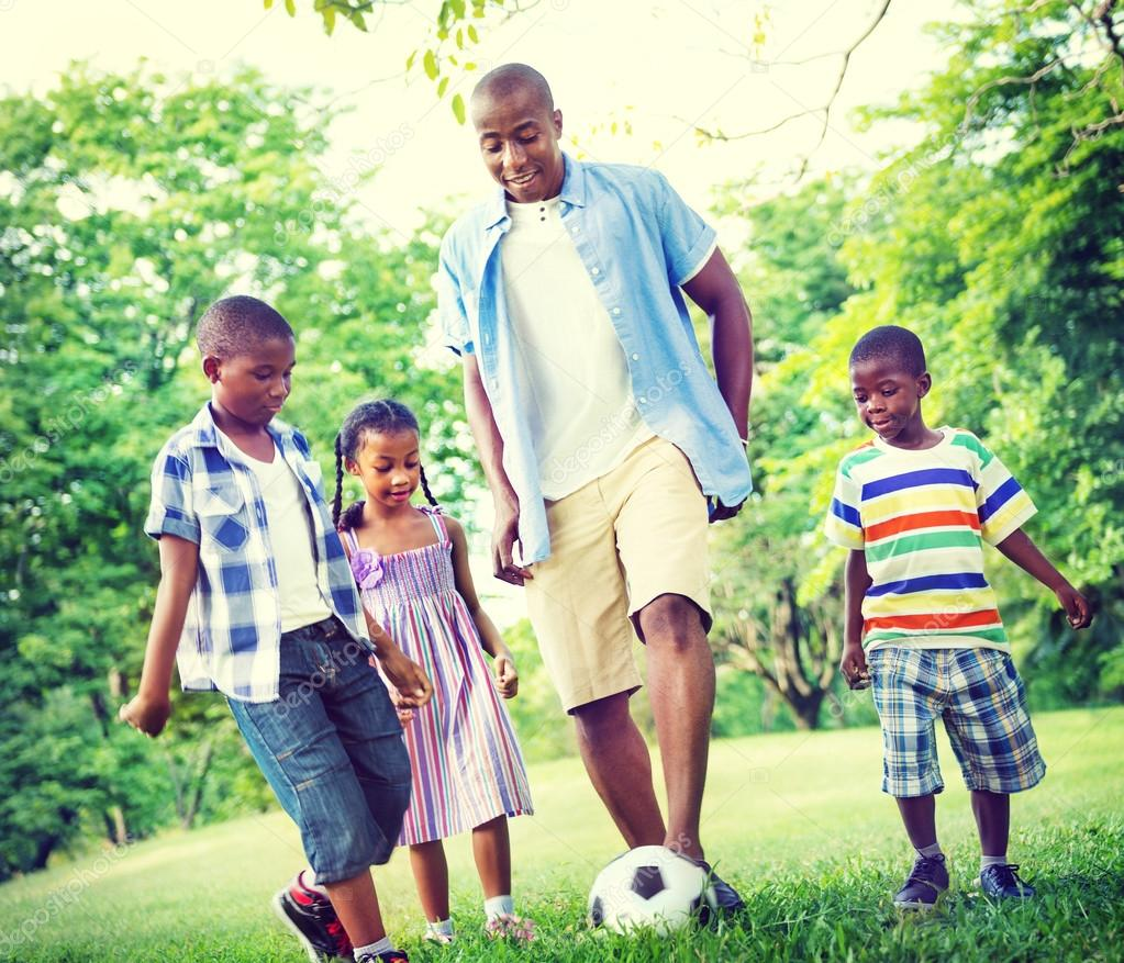 father and his sons and daughter playing football — Stock Photo