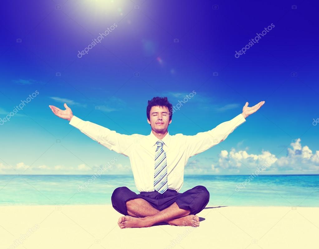 Businessman meditating on the beach Concept