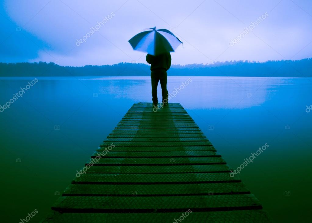 Man Holding an Umbrella at Lake