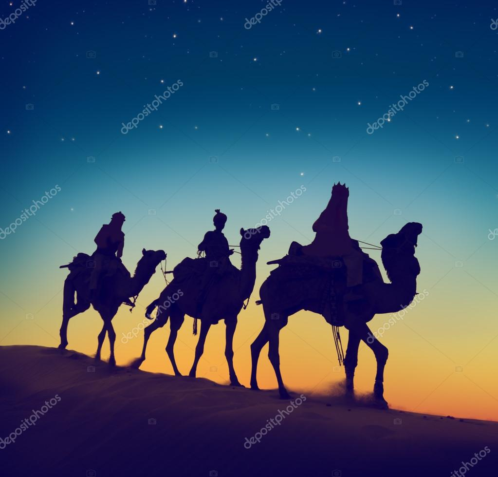Men riding camels through desert