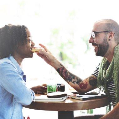 man feeding his girlfriend with donut