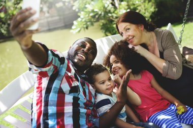 happy family taking selfie with smartphone